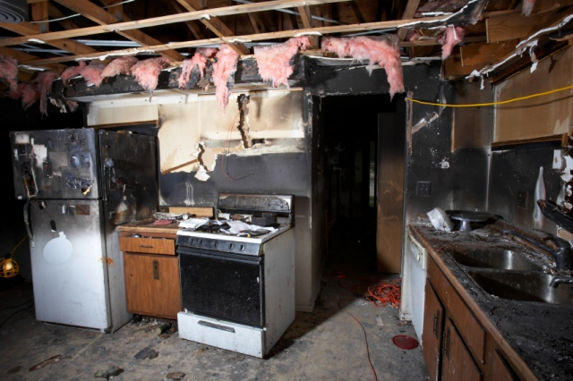 kitchen after fire with smoke damage and drywall exposure